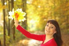 Uśmiechnięta kobieta z liśćmi klonowy w ręce Obraz Stock