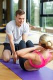 Uśmiechnięta kobieta z męskim trenerem ćwiczy w gym Fotografia Royalty Free