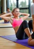 Uśmiechnięta kobieta z męskim trenerem ćwiczy w gym Fotografia Stock