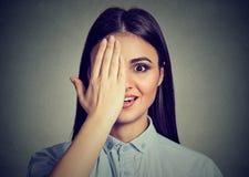 Uśmiechnięta kobieta z okiem, zamykał ręką, nakrywkowa część jej twarz Zdjęcie Stock