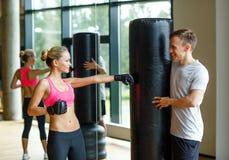 Uśmiechnięta kobieta z osobistym trenera boksem w gym Zdjęcia Stock