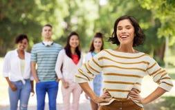 Uśmiechnięta kobieta z rękami na biodrach nad lato parkiem zdjęcia stock