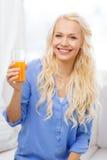 Uśmiechnięta kobieta z szkłem sok pomarańczowy w domu Zdjęcia Stock