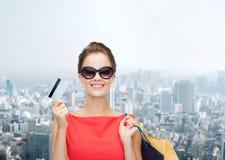Uśmiechnięta kobieta z torba na zakupy i klingeryt kartą fotografia stock