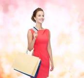 Uśmiechnięta kobieta z torba na zakupy i klingeryt kartą Zdjęcia Royalty Free