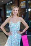 Uśmiechnięta kobieta z torba na zakupy i rękami na biodrach Zdjęcia Royalty Free