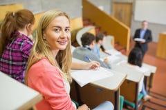 Uśmiechnięta kobieta z uczniami i nauczycielem przy odczytową sala obrazy stock