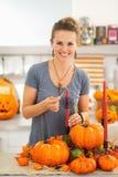 Uśmiechnięta kobieta zaświeca świeczkę w Halloween dekorował kuchnię Zdjęcia Royalty Free
