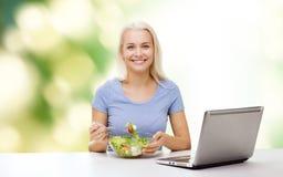 Uśmiechnięta kobiety łasowania sałatka z laptopem Zdjęcia Stock