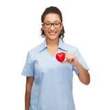 Uśmiechnięta kobiety lekarka, pielęgniarka z sercem lub Obrazy Stock