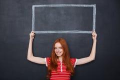 Uśmiechnięta kobiety mienia rama rysująca na blackboard nad jej głowa Obraz Royalty Free