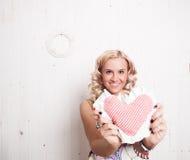 Uśmiechnięta kobiety mienia serca poduszka Zdjęcie Stock