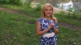 Uśmiechnięta kobiety obwąchania woń chamomile patrzeć niebo i kwiaty zdjęcie wideo