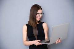 Uśmiechnięta kobiety pozycja z laptopem nad szarym tłem Fotografia Stock