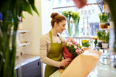 Uśmiechnięta kwiaciarni kobieta pakuje wiązkę przy kwiatu sklepem Obraz Royalty Free