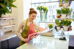 Uśmiechnięta kwiaciarni kobieta pakuje wiązkę przy kwiatu sklepem Zdjęcie Royalty Free