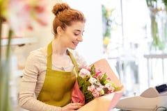 Uśmiechnięta kwiaciarni kobieta pakuje wiązkę przy kwiatu sklepem Zdjęcia Royalty Free