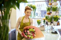 Uśmiechnięta kwiaciarni kobieta pakuje wiązkę przy kwiatu sklepem Obraz Stock