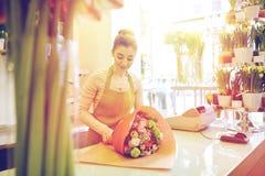 Uśmiechnięta kwiaciarni kobieta pakuje wiązkę przy kwiatu sklepem Obrazy Stock