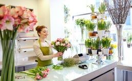 Uśmiechnięta kwiaciarni kobieta robi wiązce przy kwiatu sklepem Obrazy Stock