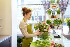 Uśmiechnięta kwiaciarni kobieta robi wiązce przy kwiatu sklepem Zdjęcie Stock