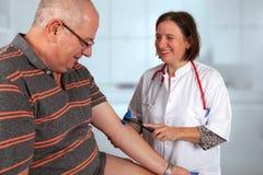 Uśmiechnięta lekarka egzamininuje biceps rozciągliwości odruch z odruchu młotem obraz stock