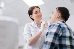 Uśmiechnięta lekarka egzamininuje bolesnego gardło obraz stock