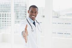 Uśmiechnięta lekarka oferuje uścisk dłoni w medycznym biurze Zdjęcie Stock