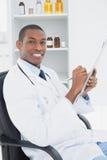 Uśmiechnięta lekarka pisze recepcie w medycznym biurze Zdjęcie Royalty Free