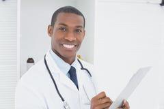 Uśmiechnięta lekarka pisze recepcie w medycznym biurze Obrazy Royalty Free