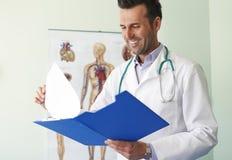Uśmiechnięta lekarka przy jego biurem Fotografia Royalty Free