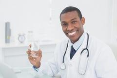 Uśmiechnięta lekarka trzyma szkło woda w medycznym biurze Obrazy Royalty Free