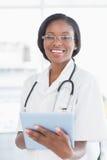Uśmiechnięta lekarka używa cyfrową pastylkę Obraz Stock