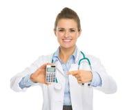 Uśmiechnięta lekarz medycyny kobieta wskazuje kalkulatora Obrazy Royalty Free