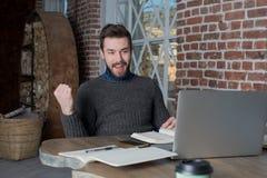 Uśmiechnięta mężczyzna freelancer dźwigania ręka w tak gescie, świętowania zwycięstwo, patrzeje na laptopie zdjęcia stock