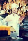 Uśmiechnięta mężczyzna masarka pokazuje kawałek mięso Zdjęcia Stock