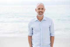 Uśmiechnięta mężczyzna pozycja morze rękami w kieszeni fotografia stock