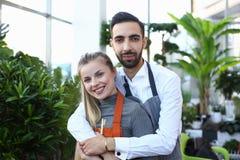 Uśmiechnięta mężczyzny przytulenia kobieta w Domowym rośliny centrum zdjęcia stock