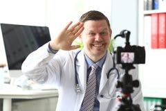 Uśmiechnięta męska millennial lekarki fala jego obraz stock