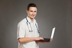 Uśmiechnięta męska pielęgniarka pozuje z laptopem Zdjęcie Stock