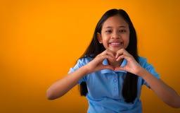 Uśmiechnięta młoda azjatykcia dziewczyna w błękitnym koszulowym pokazuje kierowym kształcie z dwa rękami obrazy stock