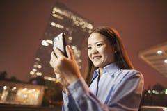 Uśmiechnięta młoda biznesowa kobieta patrzeje jej telefon komórkowego outside przy nocą Fotografia Stock