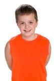 Uśmiechnięta młoda chłopiec w pomarańczowej koszula obraz royalty free