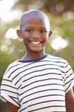 Uśmiechnięta młoda czarna chłopiec patrzeje zdala od kamery outdoors obrazy stock