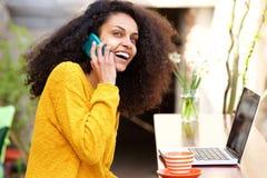 Uśmiechnięta młoda dama opowiada na telefonie komórkowym przy sklep z kawą Fotografia Stock