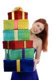 Uśmiechnięta młoda dorosła kobieta w błękitnej partyjnej sukni z stosem Bożenarodzeniowi prezenty pionowo, odizolowywający, Zdjęcia Stock
