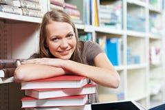 Uśmiechnięta młoda dorosłej kobiety czytelnicza książka w bibliotece obrazy stock