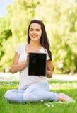 Uśmiechnięta młoda dziewczyna siedzi na trawie z pastylka komputerem osobistym Obrazy Royalty Free