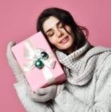 Uśmiechnięta młoda dziewczyna trzyma prezenta pudełko w pulowerze i mitynkach zdjęcia royalty free