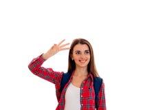 Uśmiechnięta młoda dziewczyna w czerwonej koszula i portfolio na ramion spojrzeniach przedstawienia i strona ręka gest Obraz Royalty Free